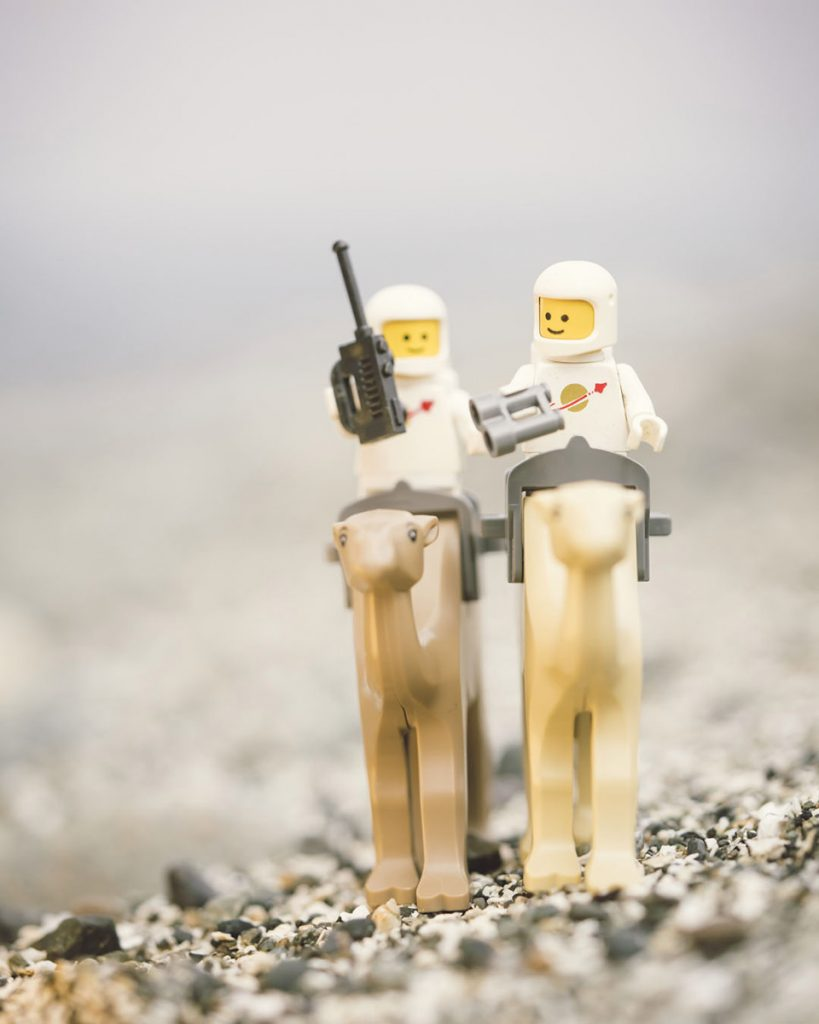 Two LEGO classic spacemen riding camels across a rocky beach. One is holding binoculars and one is holding a walkie talkie.