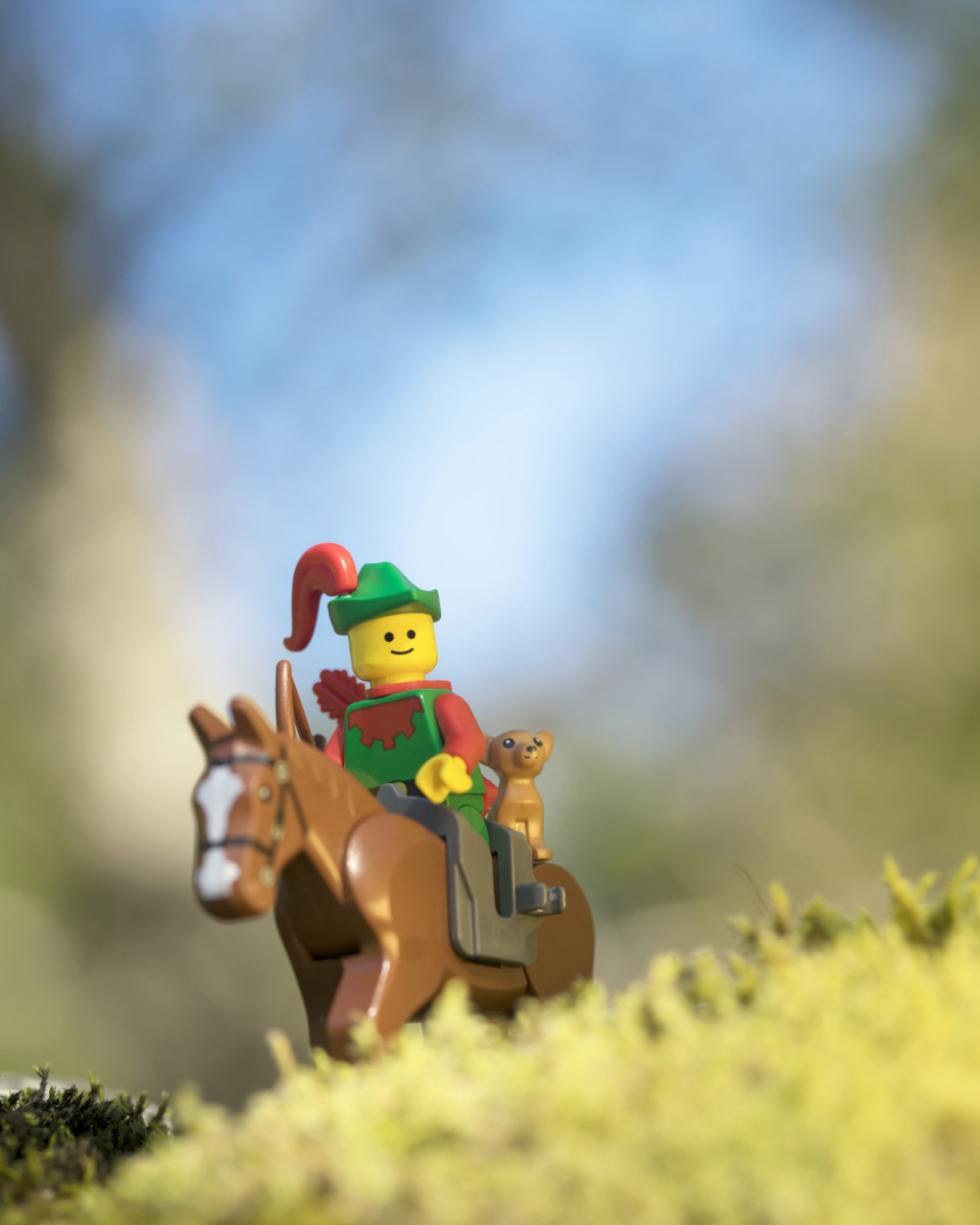 A classic LEGO woodsman riding a horse with a small dog sitting on the back of his horse.