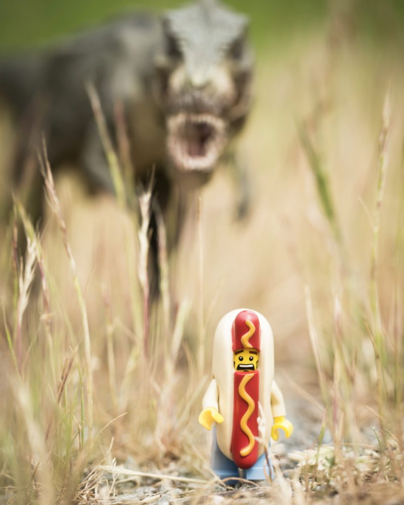 a terrified LEGO hot dog runs away from a t-Rex