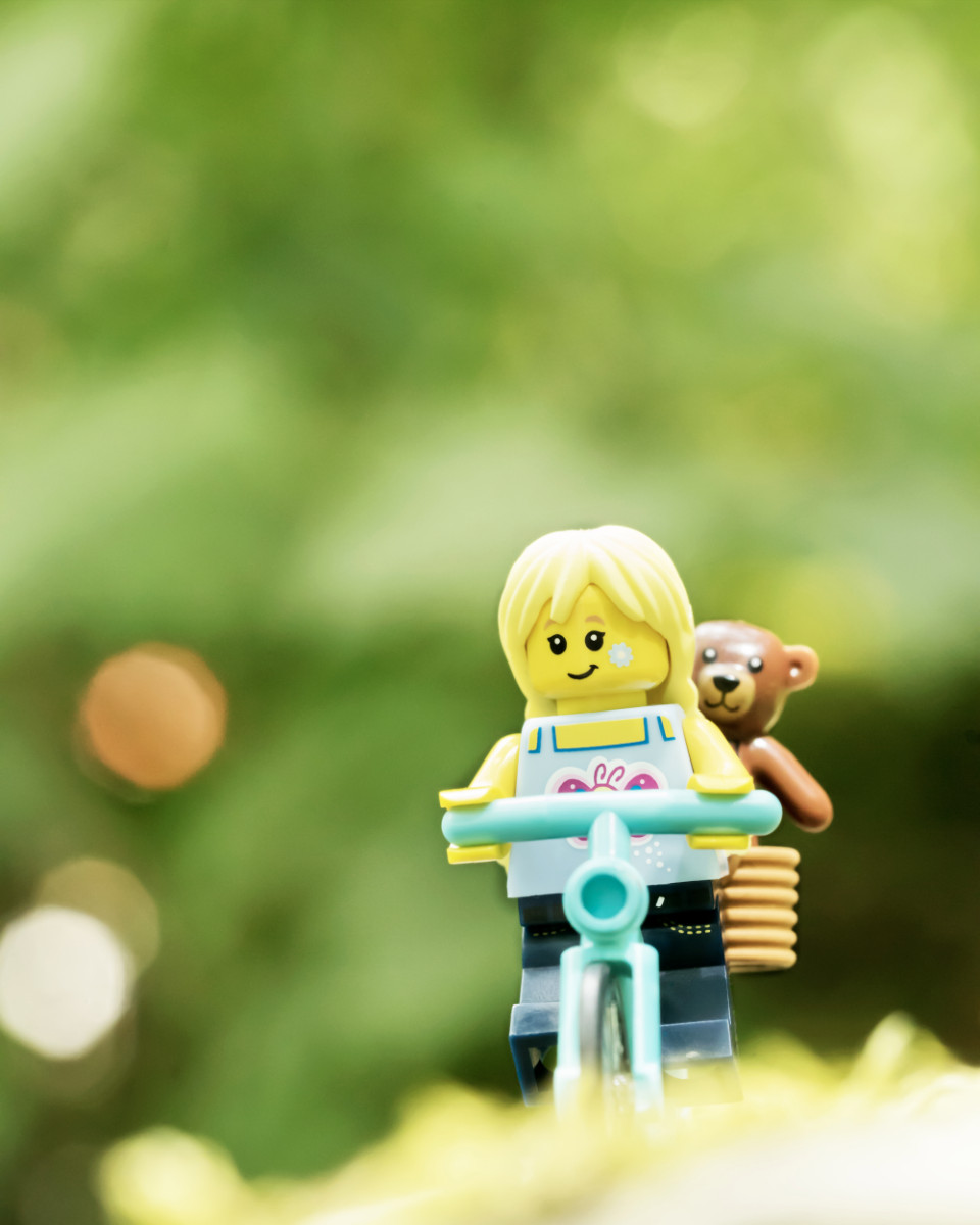 A small lego girl rides her bike with a teddy bear sitting in a basket behind her.