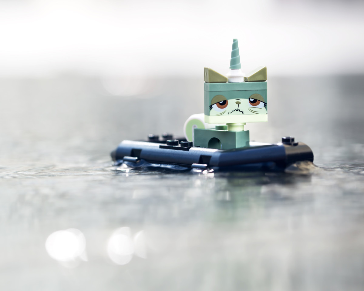 a green LEGO Unikitty stands in a boat looking sea sick.