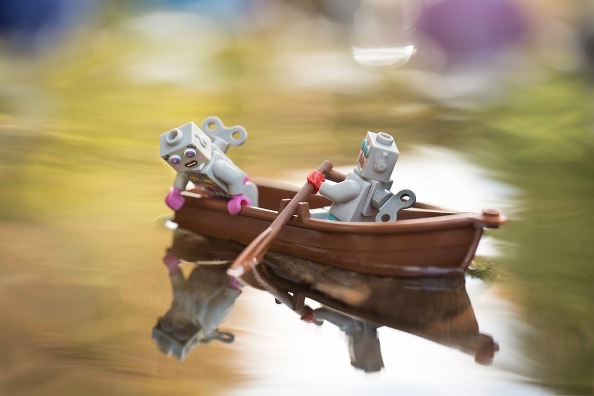 Two LEGO robots row across a pond while one looks at her reflection in the still water.
