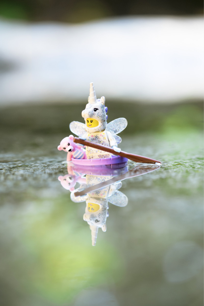 A sparkle fairy unicorn LEGO figure paddles her small boat across a pond with a pink teddy bear for company
